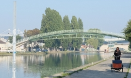 View of the Saint-Denis Canal, the Stade de France and the Fraternité footbridge in Saint-Denis (93) @ Apur