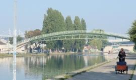 View of the Saint-Denis Canal, the Stade de France and the Fraternité footbridge in Saint-Denis (93) @ Apur